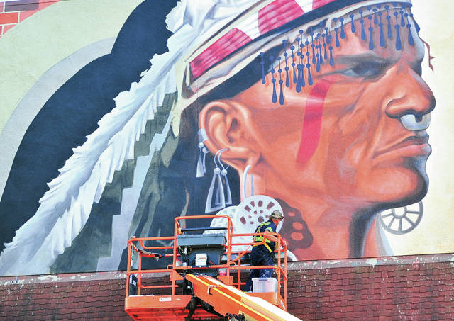 Mike Ullery | Daily Call The new mural overlooking downtown Piqua continues to take shape on the side of the building at 101 E. High St. Painted by Franklin-based artist Eric Henn, the mural depicts a member of one of the Ohio Woodlands tribes from the Piqua area, alongside a scene from the Miami-Erie Canal.