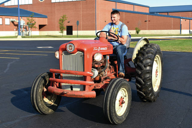 "Cody Willoughby | Troy Daily News FFA member Garrett Winner drives his tractor through the rear parking lot of Miami East High School on Wednesday during ""Drive Your Tractor to School Day."" The event is part of National Farm Health and Safety Week, which runs Sept. 16-22 and is being recognized by the Miami East School district through Friday."