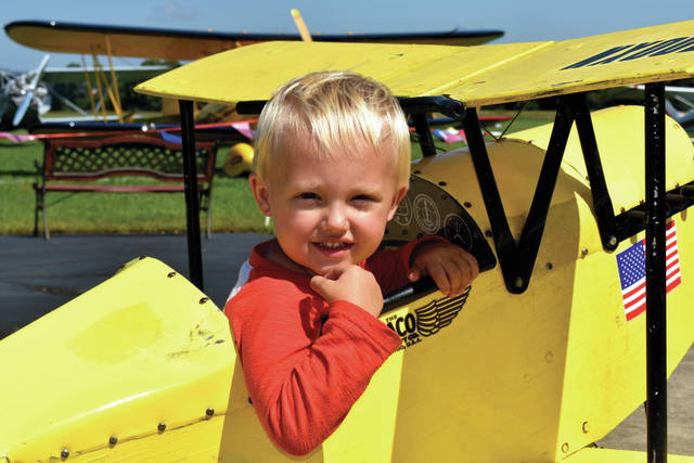 Cody Willoughby | AIM Media Jack Holtvoigt, 2, of Huber Heights, takes a ride in a pedal-plane during the WACO Vintage Fly-In on Friday. The Fly-In will be held 9 a.m. to 4 p.m. at WACO Air Museum through Sunday.
