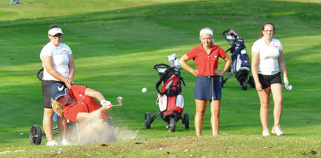Rob Kiser/Call Photo Piqua's Kelsey Bachman blasts out of a bunker on the first hole Wednesday at Echo Hills as Skylar Sloan and two Troy players watch..