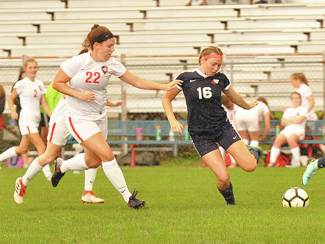 Rob Kiser/Call Photo Piqua's Shayna Bragg is pressured by Tippecanoe's Makayla Stallard (22) in the rain Monday at Wertz Stadium.