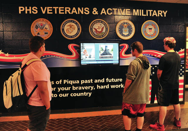 Mike Ullery | Daily Call Piqua High School sophomores Isaac Abbott, Isaiah Mears, and Isaiah Vinson check out the new Wall of Honor in the lobby of PHS. The interactive display pays tribute to alumni who have served or are currently enlisted in the Armed Forces.
