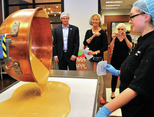 Mike Ullery | Daily Call Matt MacLaren, director of Tourism Ohio, back left, and Laurie Reiser, owner of Winans Chocolates and Coffees look on as Winans employee Kristin Gambill pours peanut butter that will be used to make buckeyes, during a tour of the business on Thursday.