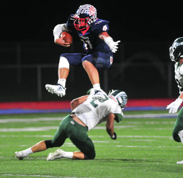 Piqua quarterback Mick Karn hurdles Greeville's John Butsch on a first-half run.