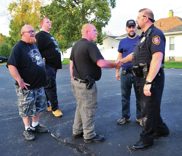 Mike Ullery | Daily Call Piqua police lieutenant Jerry Fogt shakes hands with bounty hunters who located a suspect with a nation-wide arrest warrant in Piqua on Saturday.