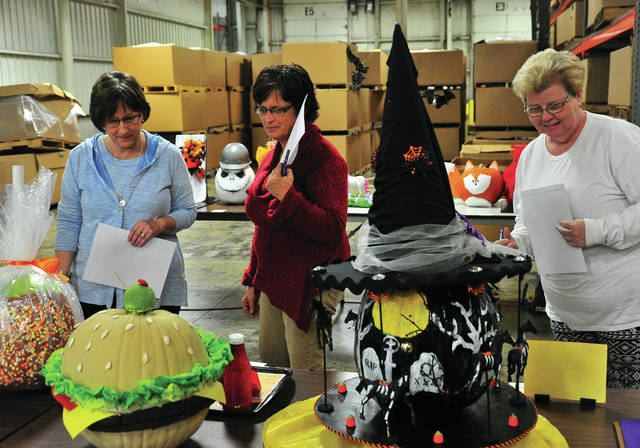 Mike Ullery | Daily Call Employees Deb Swallow, Jessica Grice, and Kay Wagner, l-r, vote on their favorite Halloween pumpkin creation at Industry Products on Thursday. The entries, which look more like works of art than pumpkins, will be donated to Piqua-area assisted living facilities to brighten their Halloween.