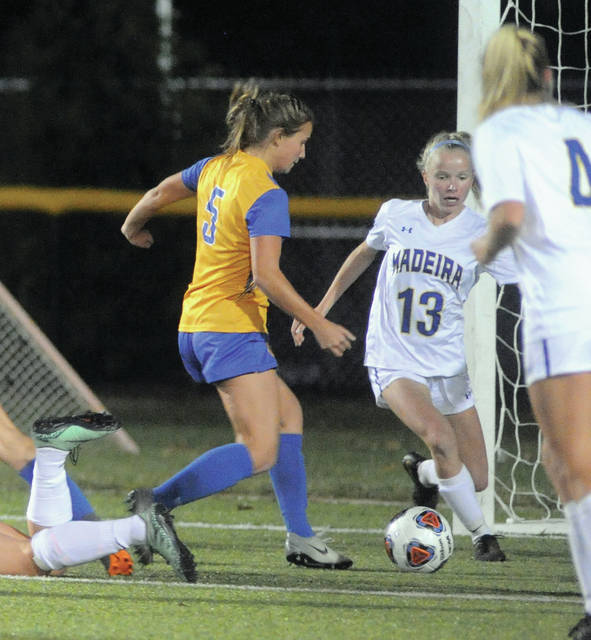 Lehman Catholic's Rylie McIver puts the ball past Madeira's Brooke Schoemaker and into the net for Lehman's first goal Tuesday night at Centerville's Alumni Field.