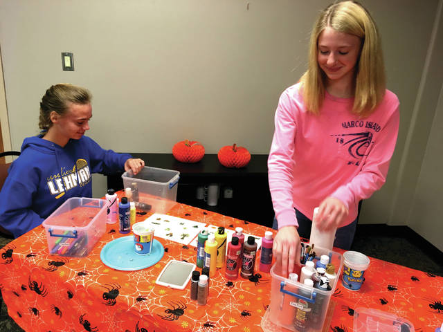 Cody Willoughby | AIM Media Midwest Junior volunteers Mary and Sarah Lins, of Troy, prepare the face-painting station at Brukner Nature Center. The station is part of the Haunted Woods event at the center, which will be held Saturday, Oct. 27, and Sunday, Oct. 28.