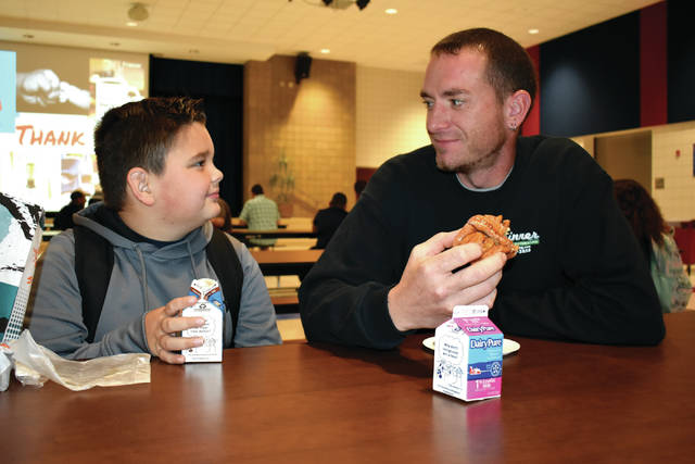 Cody Willoughby | AIM Media Midwest Fourth grader Eli Wilson enjoys breakfast with father Jeremy Wilson during 'Donuts with Dads' on Monday at Piqua Central Intermediate School.