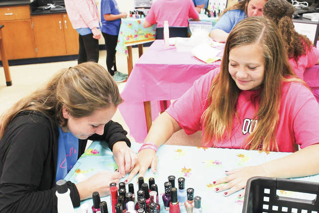 "Provided photo Piqua Junior High School eighth grade teacher Emily DeBella, left, polishes student Ali Helmandollar's nails during the school's recent ""Girls Night Out."" Guidance counselor Toni Riley coordinated the evening, which offered several different stations the girls could visit including Yoga, Self-defense, Healthy Eating, Hair, Nails, Facials, Positive Imaging, and Game Night."
