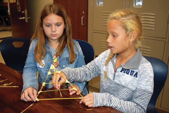 Cody Willoughby | AIM Media Midwest Fifth graders Brooklyn McGuire and Kamari Evans construct a pasta bridge truss druing STEM Day on Tuesday at Piqua Central Intermediate School.