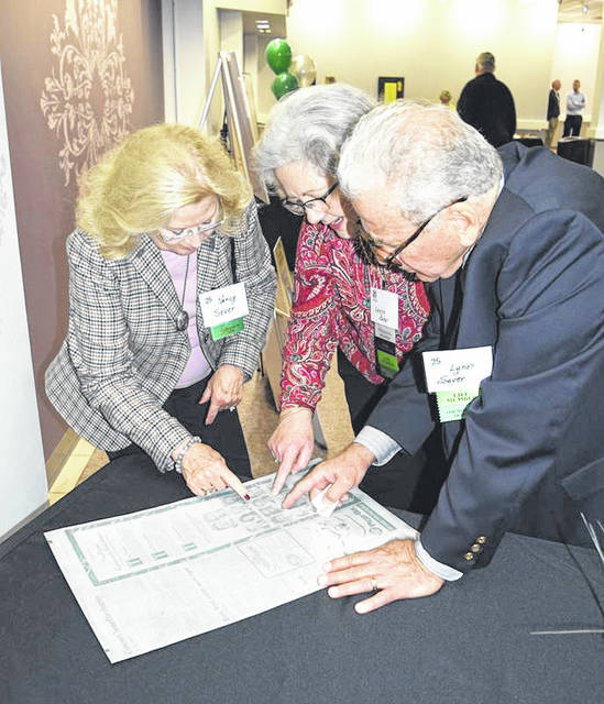Provided photo Founding board member Leesa Baker, center, shares with Nancy and Lynn Sever the original tin press plate from the <em>Piqua Daily Call</em> from 1994 announcing the establishment of The Piqua Community Foundation.