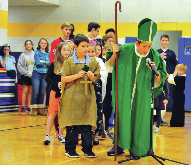 "Donovan O'Leary, a seventh-grader at Piqua Catholic School dresses as Saint Patrick for Thursday's All Saints Day Parade at the school. The annual event honors ""all saints, known and unknown,"" said principal Brad Zimmerman, "" To celebrate here at Piqua Catholic School, we allow our students to dress as a saint to recognize their devotion to God and the Catholic faith."""