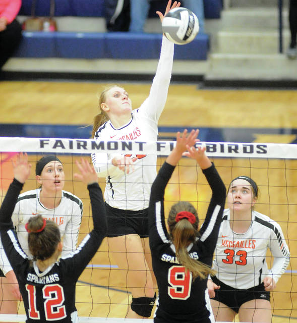 Versailles' Liz Ording hits a kill as Kelsey Custenborder (33) and Lindsey Winner (25) look on Saturday against Marion Pleasant at Trent Arena.