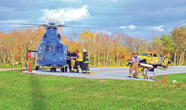 Mike Ullery | Daily Call Firefighters and medics load a patient for transport at the scne of Tuesday's crash on Co. Rd. 25-A at Troy-Sidney Road.