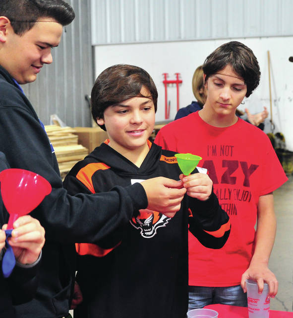 Mike Ullery | Daily Call Kaden Power, Diego Remirez-Huffman, and Aidan Cowis, make homemade stress balls during a visit to Crayex Corporation on Friday. Piqua Junior High School students visited the plastic products manufacturer to learn about products produced in their home town.