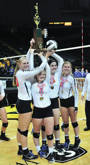Mike Ullery|Daily Call Versailles volleyball seniors Liz Ording, Paige Platfoot, Kelsey Custenborder and Alexa Didier hold up the D-III state championship trophy Saturday at the Nutter Center.