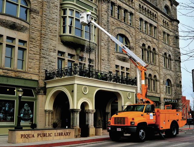 Mike Ullery | Daily Call Piqua Power crews erect a Christmas Tree made of lights on top of a portico at the Piqua Public Library on Wednesday.