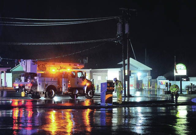 Dayton Power and Light crews work on power lines that were brought down by ice on South Dorset at McKaig Ave. in Troy early Thursday morning.