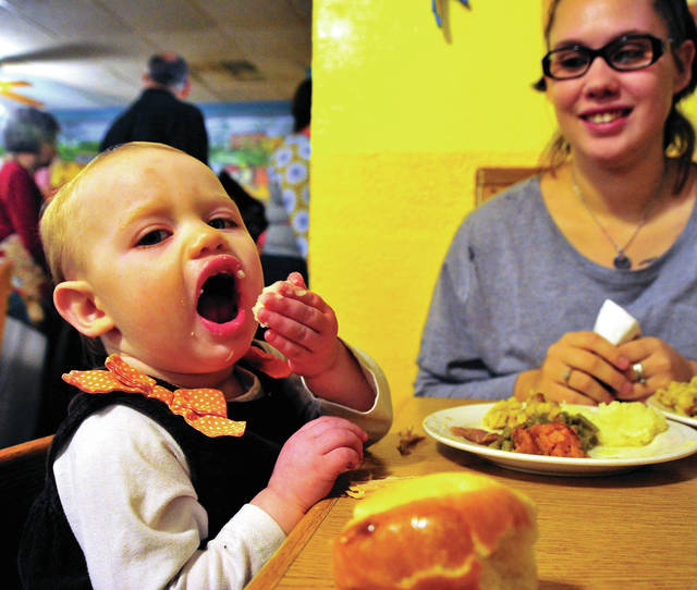 Mike Ullery | Daily Call Skylar Sebastian, 1, of Piqua enjoys her first Thanksgiving dinner at El Sombrero in Troy as her mom Desiree watches.