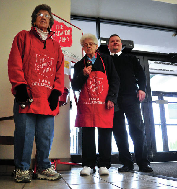 "Mike Ullery | Daily Call Donna Lemmon, 84, and her sister Norma Lyons, 92, man the Salvation Army kettle at the Miami Valley Centre Mall on Friday along with Major Robert Kramer of the Piqua Salvation Army. The mall is one of nine locations in Piqua, and two in Troy, where bell-ringers continue the 128 year old tradition of raising money for those in need. Major Kramer said that, in spite of the upturn in our economy ""there are still many in need"" of help around the Christmas season."