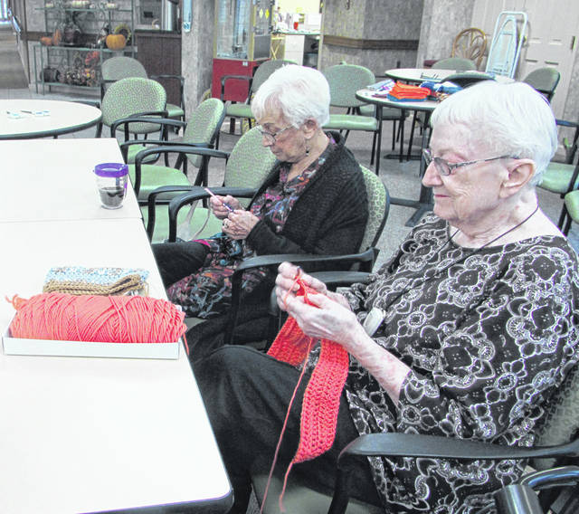 Sam Wildow | Miami Valley Today Middy Smith (right) and Betty Cohee (left), of the St. James Episcopal Church knitting group, crocheting scarves for local school kids.