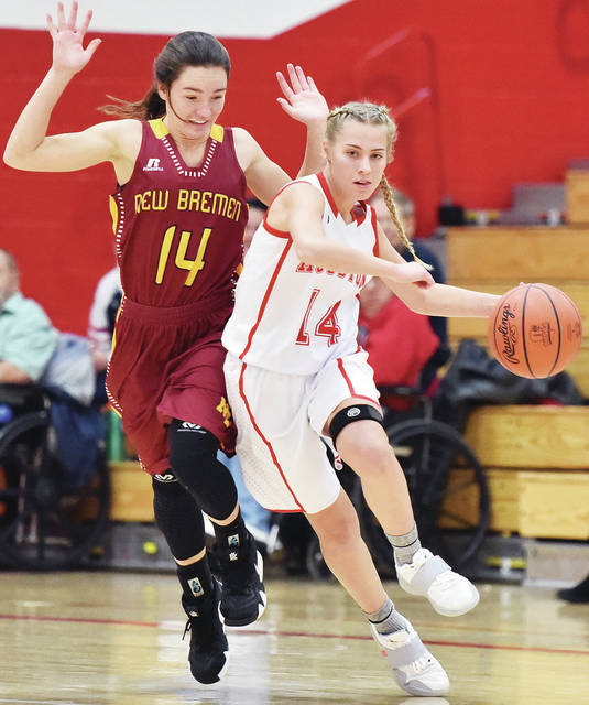 Luke Gronneberg|Aim Media Photo Houston's Hollie Voisard drives past New Bremen's Abbi Thieman Thursday night at Houston High School.