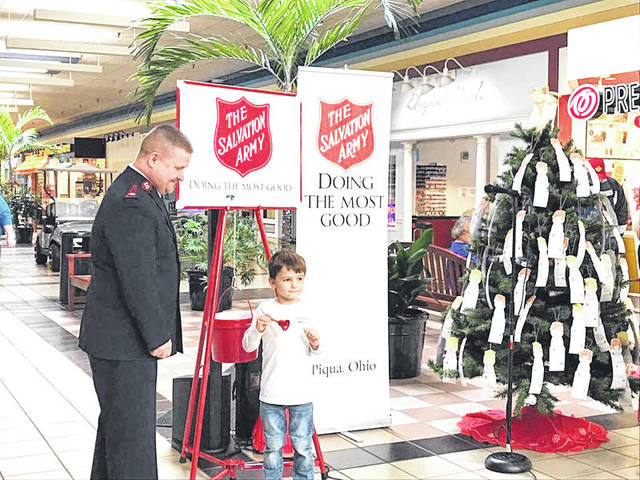 Provided photo Max Peterson of Piqua helps Maj. Robert Kramer of the Piqua Salvation Army ring the bell for the launch of the local Red Kettle season to help those in need.
