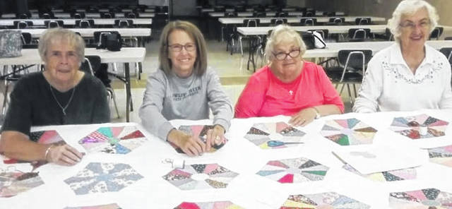 Provided photo Members of St. Boniface and St. Mary parishes spent many hours working on the Dresden Plate Quilt to be raffled on Dec. 1. Pictured from left to right are Janet Poling, Betty Elliott, Cindy Nelson, and Dolores Latham.