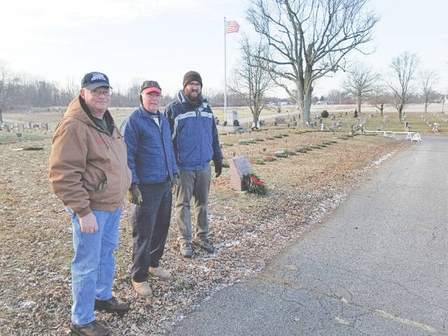Provided photo Dana Babcock, Jim Robinson and Ben Zimmerman place wreaths in the veterans' section of Forest Hill Cemetery last December.