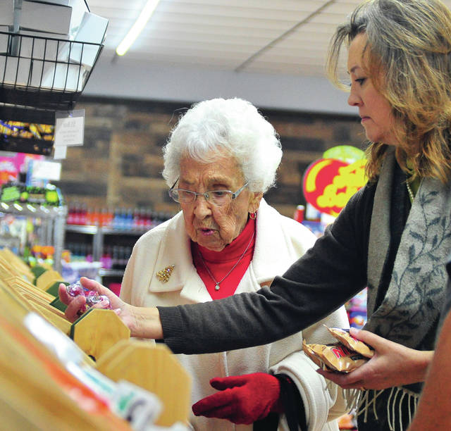 Mike Ullery | Daily Call Mary Baker, 102 years young, checks out the candy selection at This & That's Candy during a pre-opening event, with her granddaughter Melinda McBride on Tuesday evening. The candy story, located at 409 N. Main St., opens to the public on Friday.
