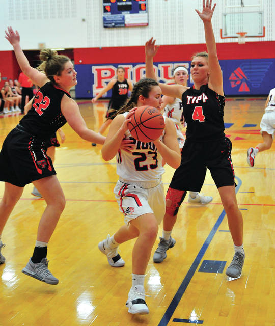 Piqua's Kenzi Anderson, clears a rebound between Tippecanoe's Olivia Newbourn (22) and Mackenzie Smith (4).