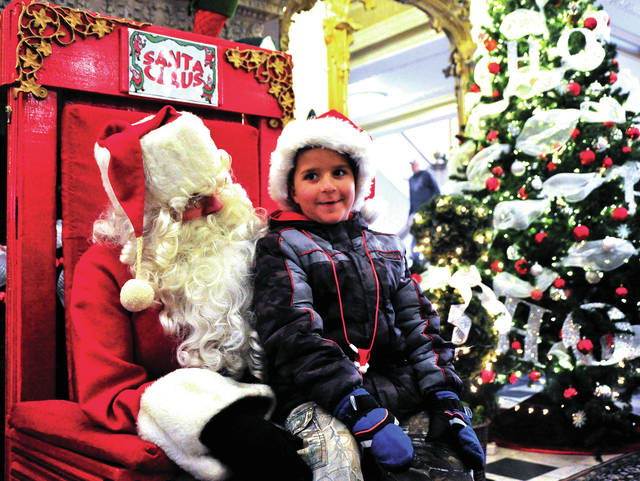Jack Grise, 6, of Piqua lets Santa know what he wants for Christmas during a visit to the Piqua Public Library on Saturday