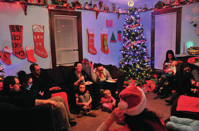 Mike Ullery | Daily Call Adams Street residents gather in the living room of Joe Quinn on Saturday evening for the neighborhood's second annual Christmas block party.