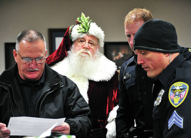 Santa Claus keeps watch as Miami County FOP members, Jim Waysong, Adam Simpson, and Ryan Omberg check their list … twice … as Santa prepares to accompany FOP members to deliver Christmas packages to families whose lives have been touched by crime during the past year.