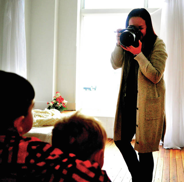 Hannah Wenrick, owner of Hannah Wenrick Photography, works on a portrait in her new studio at 116 W. Water St. in Piqua this week.