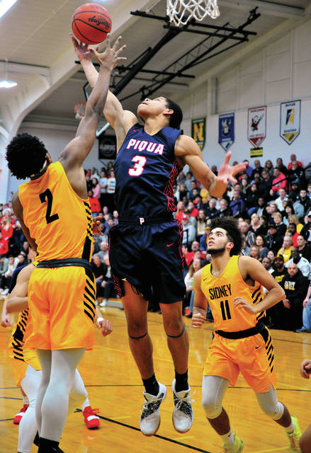 Piqua's Trey Richmond grabs a rebound between Ratez Roberts (2) and Keith Lee Friday night.