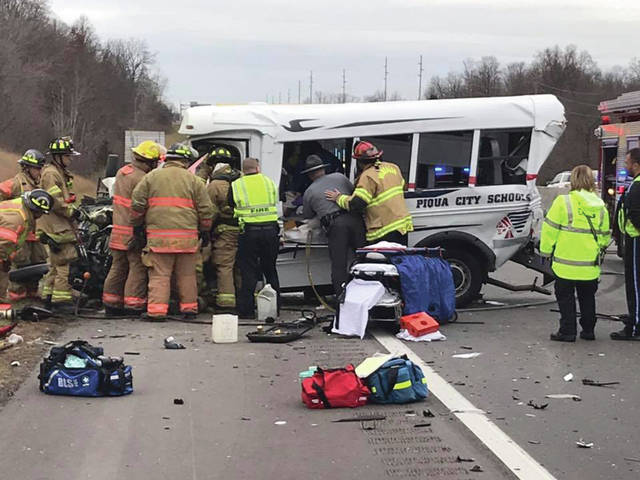 Contributed photo by the Vandalia Fire Division Firefighters, medics, and Ohio State Highway Patrol troopers work to free the driver of a Piqua City Schools bus that was involved in a crash on SB I-75 on Friday afternoon.