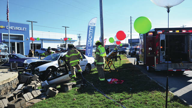 Mike Ullery | Miami Valley Today Troy firefighters extricate a crash victim from her vehicle on County Road 25-A at Joe Johnson Chevrolet on Tuesday afternoon.