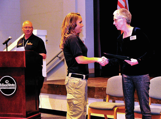 Lisa Holfinger receives her Ohio Basic Police Officer Academy graduation certificate from Dr. Doreen Larson as Academy Commander Joe Mahan looks on at Edison Community College on Tuesday. The ceremony was attended by nearly a dozen Troy Firefighters who showed up to support Holfinger whose Troy Firefighter husband passed away suddenly this summer.