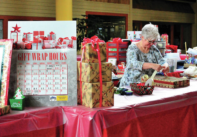 Mike Ullery | Miami Valley Today Lehman Catholic High School music parent Betsy Snyder wraps Christmas gifts at the Lehman Music Boosters booth at the Miami Valley Centre Mall on Monday. The annual fundraiser is available to customers through Christmas Eve. Gifts need not be purchased at the mall.