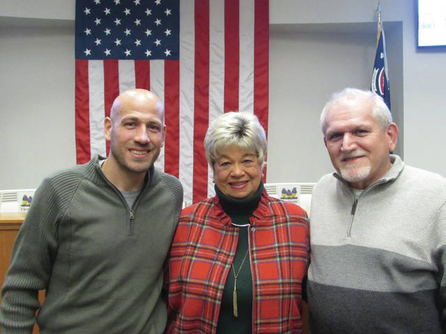 Sam Wildow | Miami Valley Today Becky and Steve Cool (center and right) with their son, Ryan, after Becky and Steve's last night working at a Piqua City Commission meeting on Dec. 18.