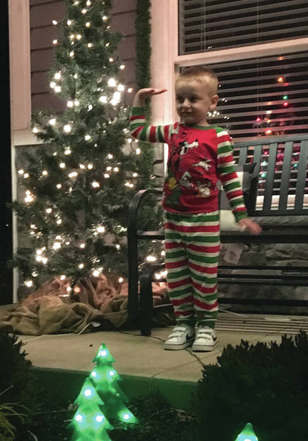 Cody Willoughby   Piqua Daily Call Cannon Widney, 4, of Piqua greets passersby in his Christmas pajamas during the third annual Indian Ridge luminary lights and decorating contest on Friday. Over 16,000 lights on 160 trees lined the entrances of Indian Ridge during the event, with nearly 1,200 luminary kits distributed to line the sidewalks of the neighborhood.