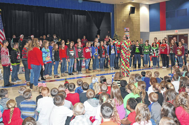 "Cody Willoughby | Piqua Daily Call Piqua High School show choir director Tom Westfall leads ""The Company"" in an a capella rendition of ""Carol of the Bells"" during a visit to Washington Primary School on Tuesday."