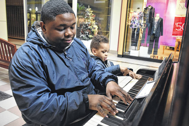 Cody Willoughby | Piqua Daily Call Tray and Zayden Collins, of Dayton, tap out a tune on an 1890s New York Weber on Thursday at Miami Valley Centre Mall. The piano, along with an 1890s Packard Upright, are available for public usage during regular mall hours.