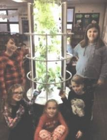 Students gather around the Tower Garden in Kathy Irick's fourth grade classroom at Miami East Elementary. Students shared their favorite learning experiences with the Tower Garden by writing a story about it. The authors, pictured here, were Joselyn Rowe, Alyssa Siefring, Alivia Palivec, Lincoln Littlejohn and Charley Hatcher.
