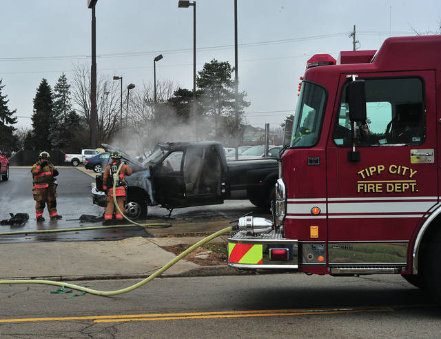 Mike Ullery   Troy Daily News Firefighters from Tipp City extinguish a truck fire in the parking lot of the Hickory River restaurant on Garber Drive on Wednesday morning. A dog was reportedly trapped in the truck for a brief time but was freed and uninjured.