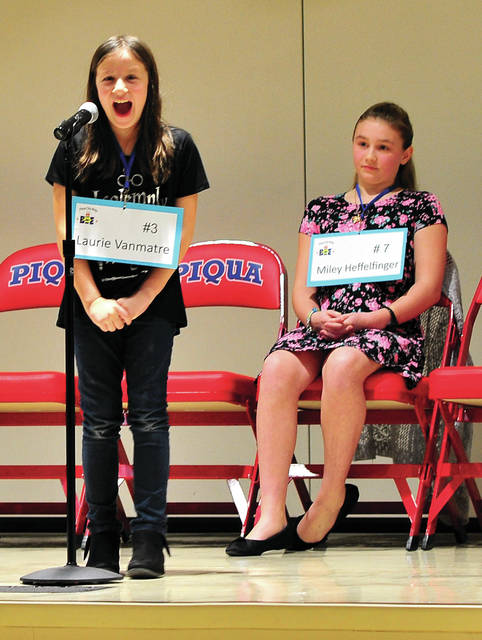 Mike Ullery | Daily Call Laurie Vanmatre, a third-grade student at Springcreek Elementary School, reacts to winning the 2019 Piqua City-Wide Spelling Bee at PCIS on Thursday. Pictured with Vanmatre is runner-up Miley Heffelfinger from Piqua Catholic School.