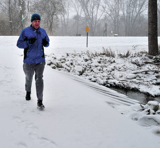 Mike Ullery |Daily Call Todd Lewis of Casstown enjoys a morning run in the snow along the bike path at the Miami County Park District Farrington Reserve on Saturday.