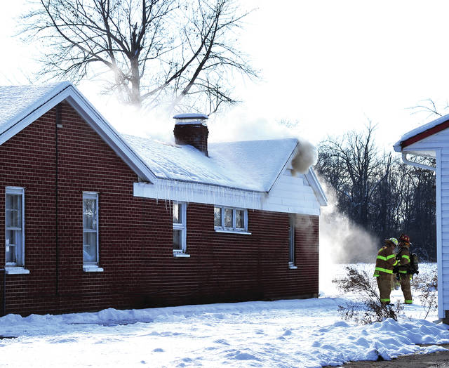 Mike Ullery | Daily Call Troy firefighters battle a fire in the attic area of a home in the 1300 block of East Main Street on Monday afternoon.
